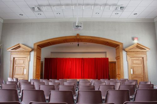 Stanback Auditorium with chairs and red curtain set up