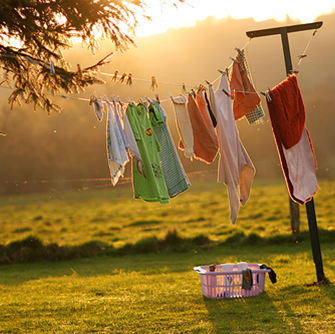 Laundry hanging on a clothes line in a yard at sunset.