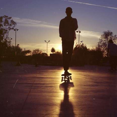 Silhouette of a teen male on a skateboard rolling away on a paved surface into the sunset.