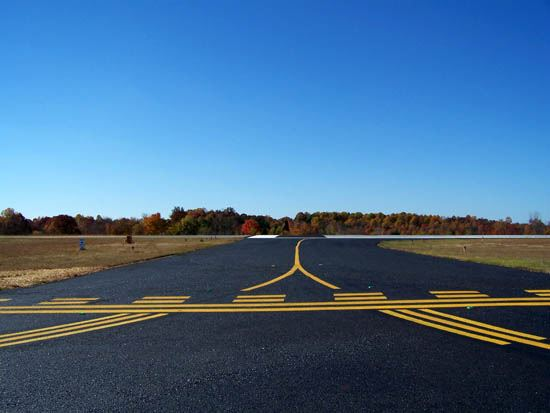 Airplane Runway With Yellow Lines and Trees in the Background