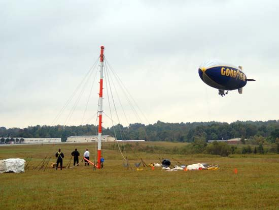 Good Year Blimp Going over Field with Ground Crew Watching