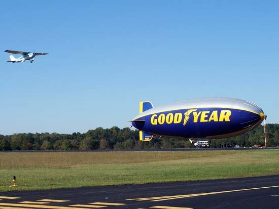 Good Year Blimp on Runway with a Plane Coming in for Landing